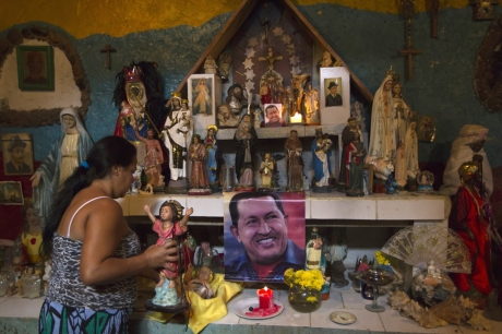 Nancy Romero places a figurine on a religious altar with images of Venezuela's President Hugo Chavez in Caracas